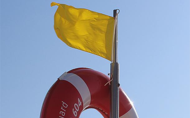 Gele vlag op het strand van Portugal